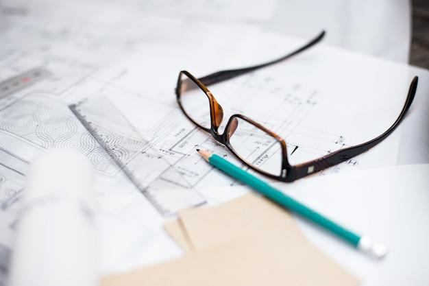 Desenhos de planejamento de construção sobre a mesa com lápis, régua e óculos sobre a mesa, efeito retro