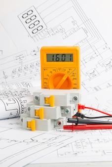 Desenhos impressos de circuitos elétricos, multímetro digital e disjuntor elétrico