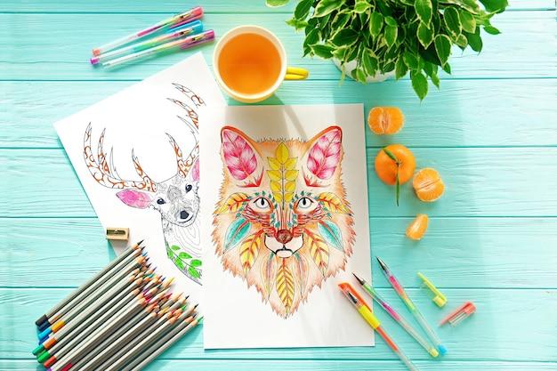 Desenhos para colorir, lápis e canetas na mesa de madeira