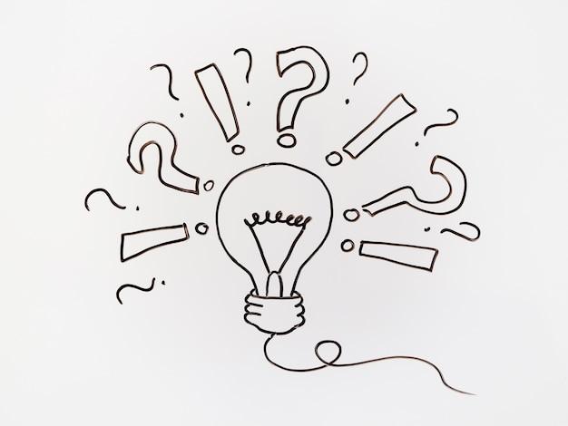 Desenhos pretos com ponto de interrogação e lâmpada