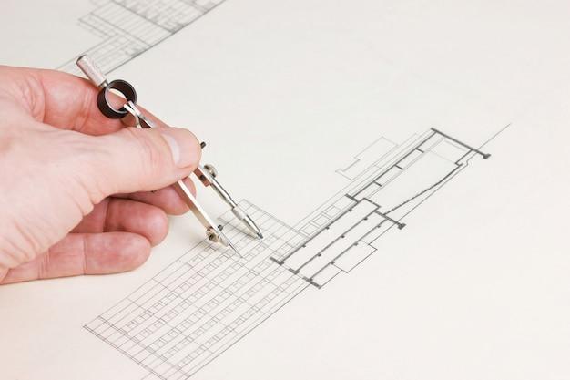 Desenhos técnicos e mão com um lápis