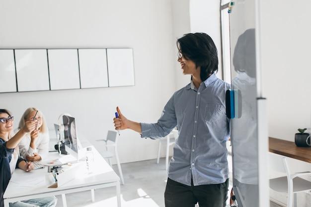 Desenvolvedor asiático em pé perto do flipchart e olhando para uma mulher loira de óculos. retrato interior do empresário morena escrevendo gráfico no quadro branco e ouvindo colegas.
