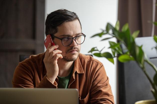 Desenvolvedor cansado trabalhando com laptop e ligando para o celular em casa