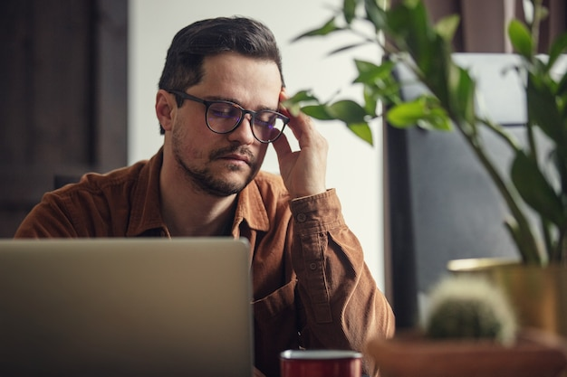 Desenvolvedor cansado trabalhando com laptop em casa