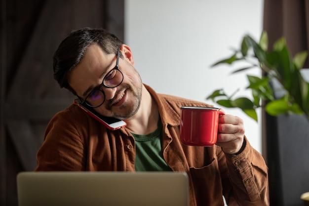 Desenvolvedor cansado trabalhando com laptop, tomando café e ligando do celular em casa