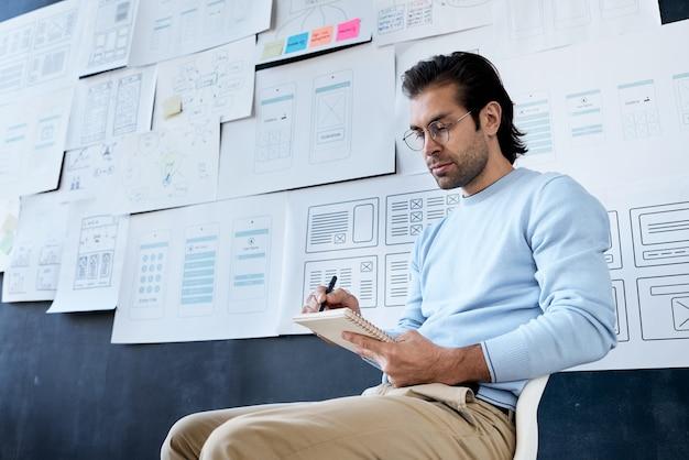 Desenvolvedor de aplicativos fazendo anotações