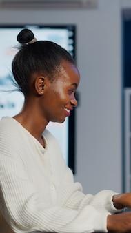 Desenvolvedor de jogos freelancer negro digitando no teclado, desenvolvendo um novo nível de videogame. jogador profissional africano que testa o jogo sobre a interface de nível à meia-noite do escritório de negócios usando o laptop.