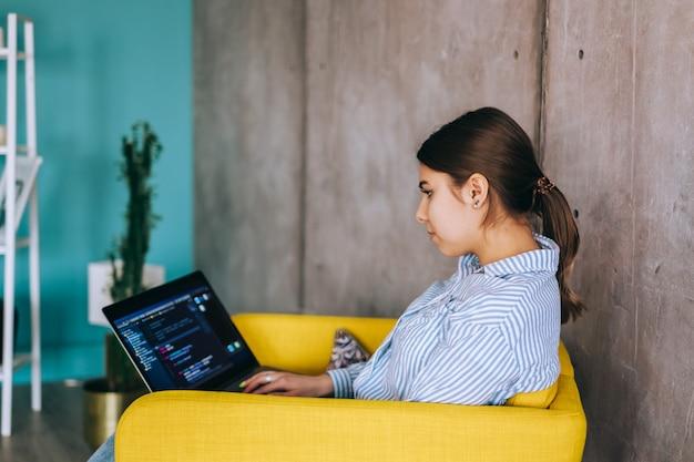 Desenvolvedor móvel jovem com laptop, escreve o código do programa em um computador, trabalho de programador em um escritório moderno.