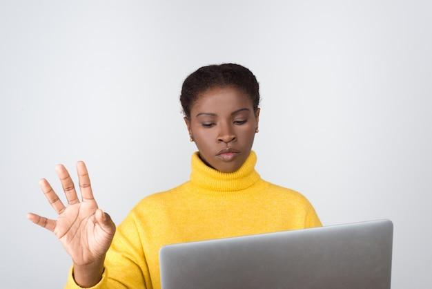 Desenvolvedor pensativo segurando laptop e tocando a tela virtual