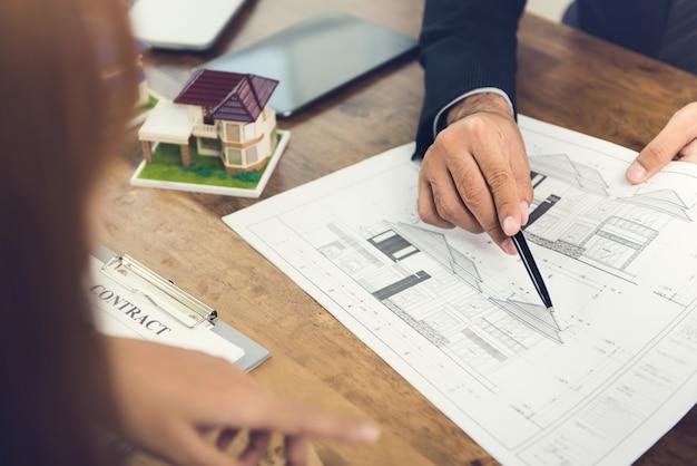 Desenvolvedor que explica um conceito de moradia a uma mulher de negócios para fins de incorporação imobiliária