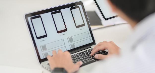 Desenvolvedor web profissional da interface do usuário trabalhando no aplicativo de smartphone com computador portátil