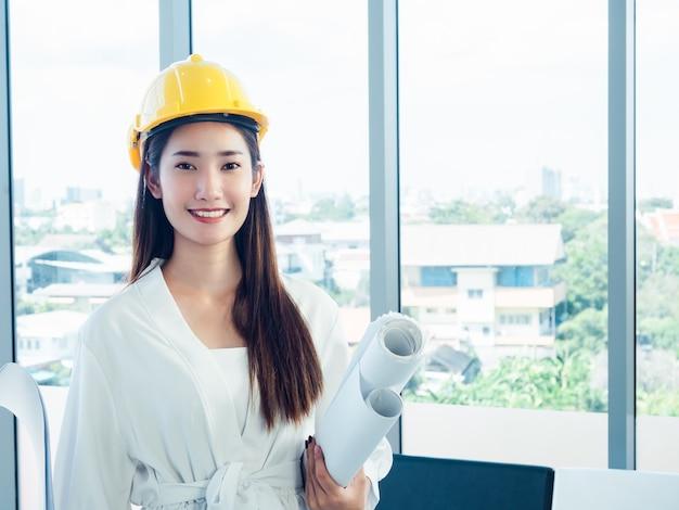 Desenvolvedora de engenheira asiática feliz usando capacete de segurança amarelo segurando papéis de projeto no vidro da janela