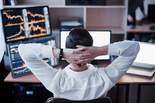 Desenvolvendo novas abordagens. vista traseira do jovem com roupa casual, segurando a mão na parte de trás da cabeça e trabalhando enquanto está sentado na mesa do escritório criativo