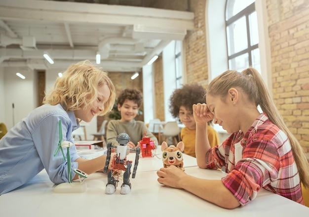 Desenvolvimento alegre de crianças diversas sentadas à mesa olhando para brinquedos técnicos cheios de detalhes