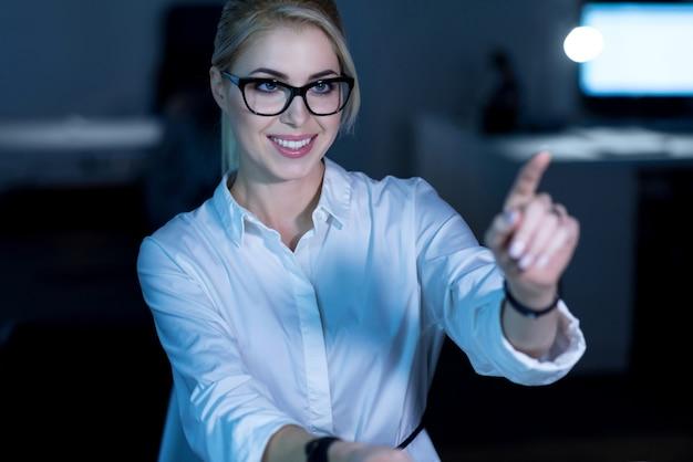 Desenvolvimento de nova linguagem de programação. jovem sorridente profissional de ti sentada no escritório usando tecnologias modernas enquanto trabalhava no projeto