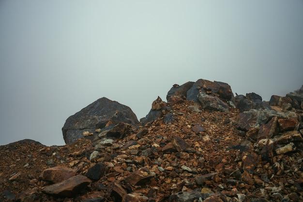 Deserto de pedra vazio perto da borda do abismo em neblina espessa. visibilidade zero nas montanhas. borda do abismo em denso nevoeiro nas terras altas. fundo de natureza minimalista. paisagem de montanha com nevoeiro. líquenes em pedras afiadas.