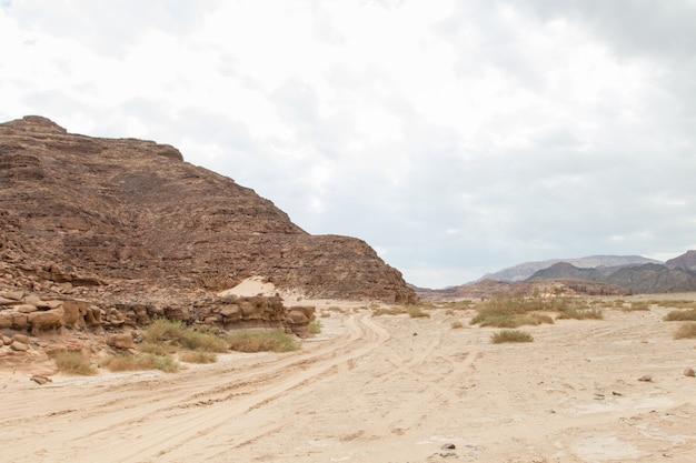 Deserto, montanhas vermelhas, rochas e céu nublado. egito, península do sinai.