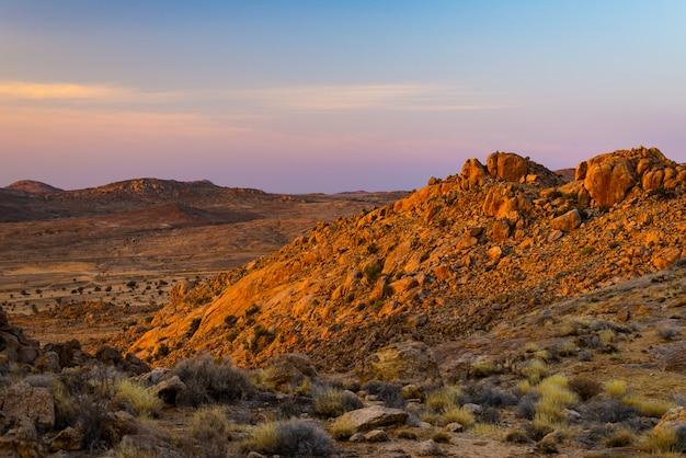 Deserto rochoso ao entardecer, pôr do sol colorido sobre o deserto do namibe, namíbia, áfrica