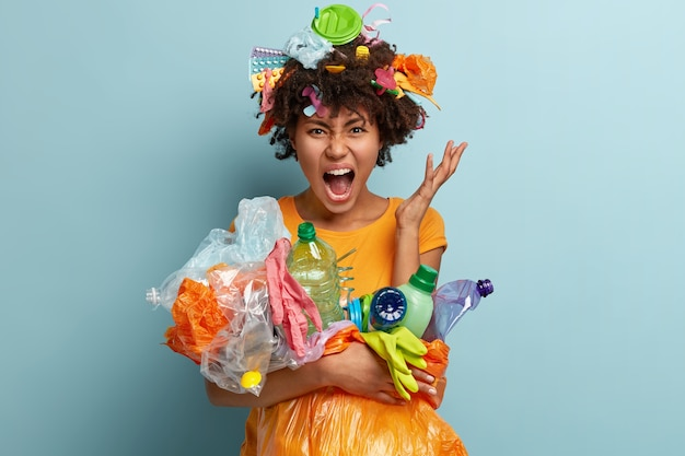Desesperada, jovem afro-americana farta da poluição, limpa o lixo, luta contra a contaminação do plástico, vestida com uma camiseta casual, gesticula com raiva, isolada contra a parede azul.