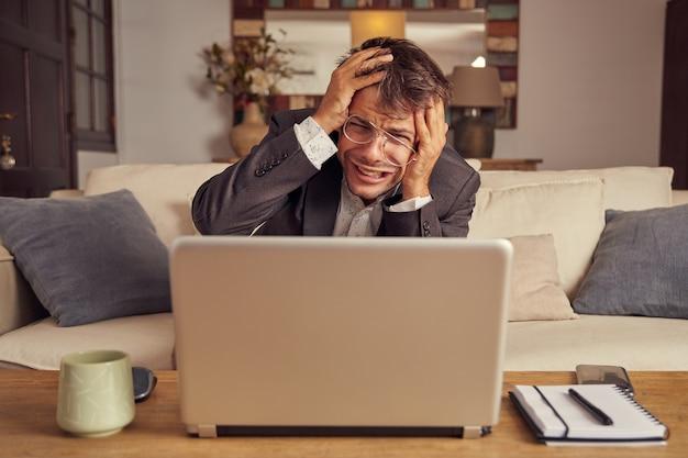 Desesperado e com raiva jovem homem caucasiano de terno, sentado em um sofá na frente de um laptop. falha no conceito de negócio. sentado no sofá em casa. mãos na cabeça.