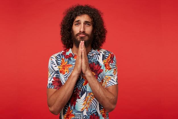 Desesperado, jovem moreno encaracolado com barba olhando tristemente para a câmera e cruzando as mãos em gesto de oração, vestido com uma camisa multicolorida com estampa floral sobre fundo vermelho