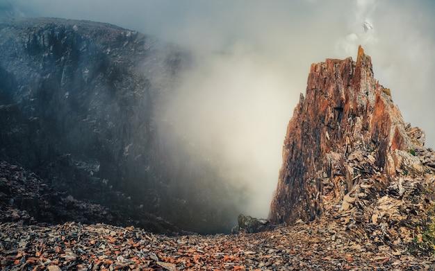 Desfiladeiro perigoso. névoa dramática entre montanhas rochosas gigantes. vista atmosférica fantasmagórica para um grande penhasco no céu nublado. nuvens baixas e belas montanhas rochosas. lugar misterioso de cenário minimalista.