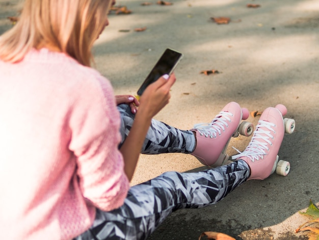 Desfocado alto ângulo de mulher de patins olhando para smartphone