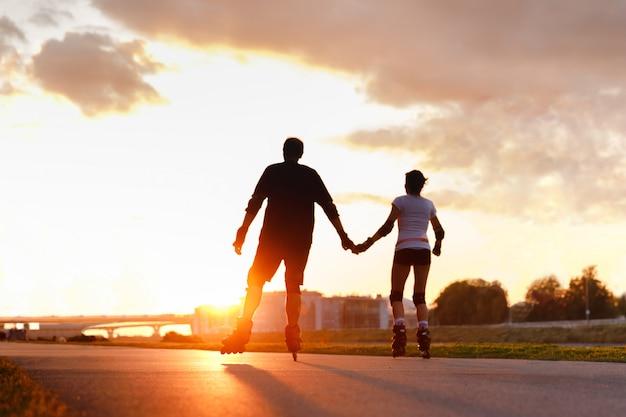 Desfocado casal andando de patins, de mãos dadas na rua durante o pôr do sol no verão, vista traseira de baixo