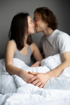 Desfocado casal de mãos dadas e beijar