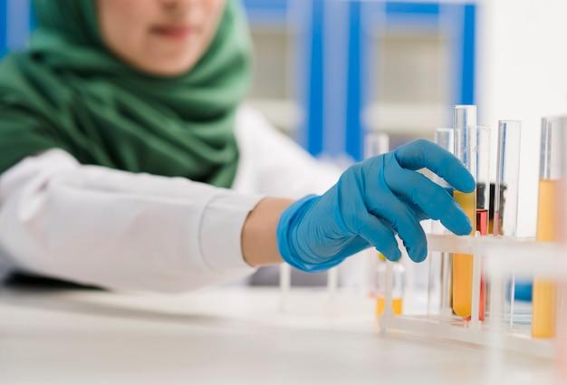 Desfocado cientista feminina com hijab trabalhando no laboratório