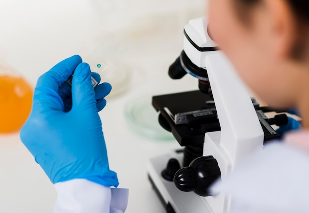 Desfocado cientista feminina com microscópio