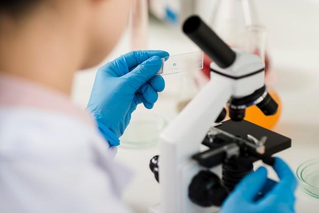 Desfocado cientista feminina olhando através do microscópio