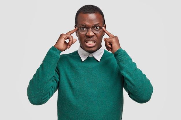 Desfocado descontente incomodado homem afro-americano adulto segura os dedos nas têmporas, tenta se concentrar, tem uma terrível dor de cabeça, trinca os dentes