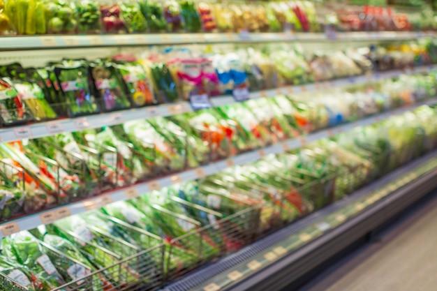 Desfocado desfocado um vegetal de prateleira de compras e frutas colocado sobre eles na comida no supermercado.