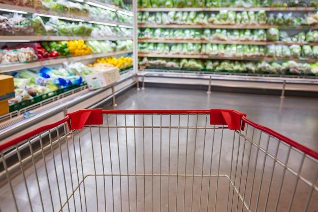 Desfocado desfoque um carrinho de compras colocado no chão de comida vegetal em um supermercado