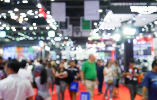 Desfocado embaçada multidão anônima pessoas andando na feira de exposições no evento de convenções ou sala de conferências. luz de fundo bokeh.