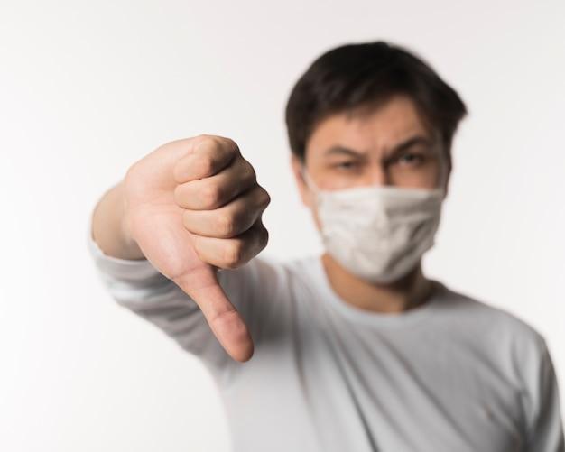 Desfocado homem doente com máscara médica dando os polegares para baixo