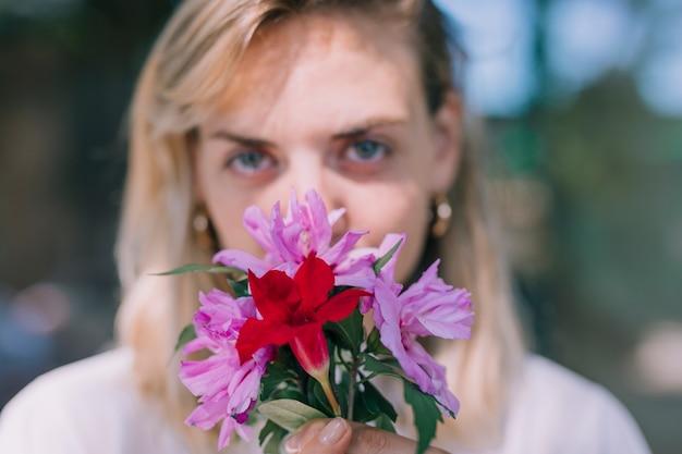 Desfocado jovem segurando o buquê de flores na frente de sua boca