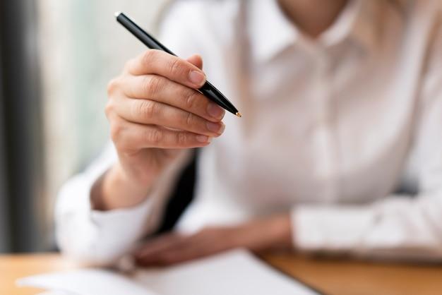 Desfocado mulher mostrando caneta close-up