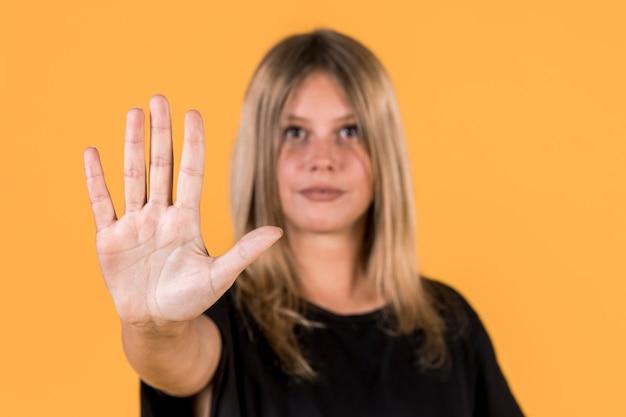 Desfocado, mulher, mostrando, parada, gesto, sinal, língua