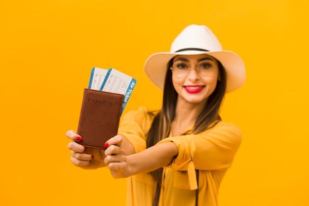 Desfocado mulher segurando bilhetes de avião e passaporte