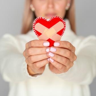 Desfocado mulher segurando coração fixa