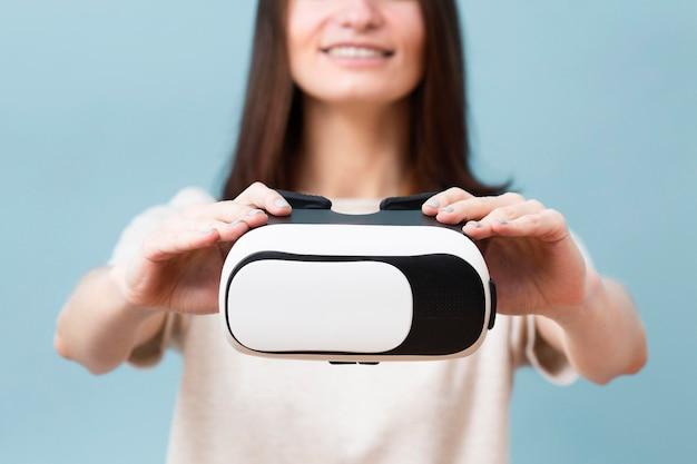 Desfocado mulher segurando fone de ouvido de realidade virtual