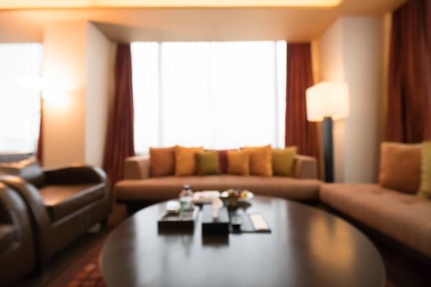 Desfocado sala de estar com mesa e sofás