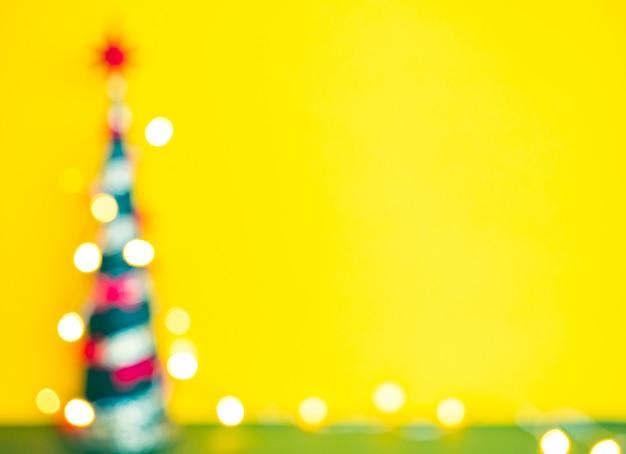 Desfocado silhueta de árvore de natal com luzes desfocadas