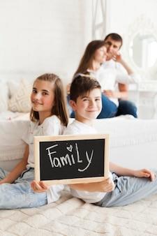 Desfocagem de casal romântico por trás do irmão segurando ardósia com texto de família