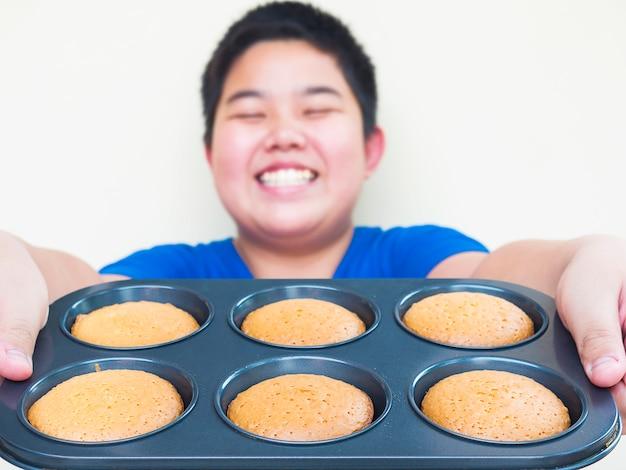 Desfocagem de garoto mostrando, servindo seus bolos caseiros.
