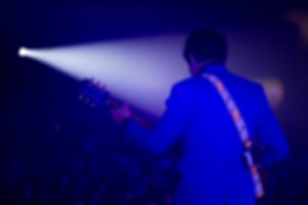 Desfocagem do guitarrista no palco para plano de fundo, colorido, foco suave e blur