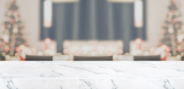 Desfocar a decoração da árvore de natal na mesa da cozinha com sala de estar em mármore