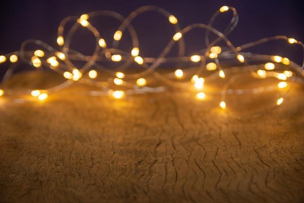 Desfocar as luzes de natal em fundo de madeira. foco seletivo em pranchas de madeira